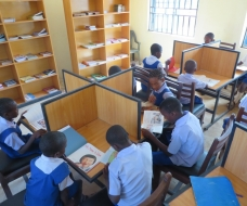 SCHOOL PUPILS IN LIBRARY STUDING PRESENTED BOOKS