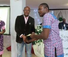Commissioner for Youth and Sports presenting a certificate to Eluke Festus