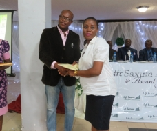 Commissioner for Youth and Sports presenting a certificate to Favour Nnaemeka