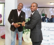 Commissioner for Youth and Sports presenting a certificate to Onyemachi Okechukwu