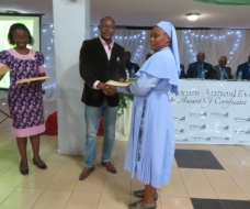 Commissioner for Youth and Sports presenting a certificate to Rev. Sr. Scholastica Okonkwo